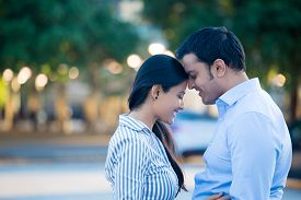 foto of enamored  - Closeup portrait young couple in blue shirt head to head eyes closed in love smitten isolated outdoors outside background - JPG