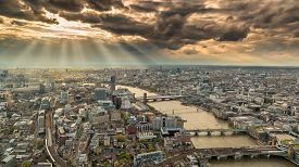 stock photo of cloudy  - Overhead view of the skyline of London in England with the river Thames against a moody and cloudy sky with the suns rays breaking though - JPG