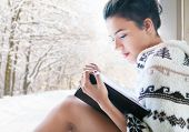 Постер, плакат: Beautiful young brunette woman reading book wearing knitted poncho sitting home by the window Blurr
