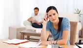 Worried Woman Doing Her Account While Her Boyfriend Waiting In The Living Room