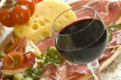 image of italian food  - glass of red wine close up with food in background - JPG