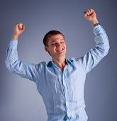 image of woohoo  - portrait of young happy man with raised hands - JPG