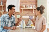 Spending Time At Home Together. Cheerful Bearded Man And His Wife Drink Tea Or Milk In Morning, Have poster