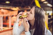Young Woman Eating Hamburger Woman Eating Junk Food, Fatty Food Hamburger poster