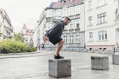 A fit young man, having endurance training in a outdoor urban space. Cardio workout. poster