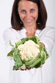 Woman proffering a whole cauliflower