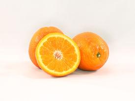 pic of tangelo  - Three ripe Minneola tangelo oranges one sliced in half - JPG