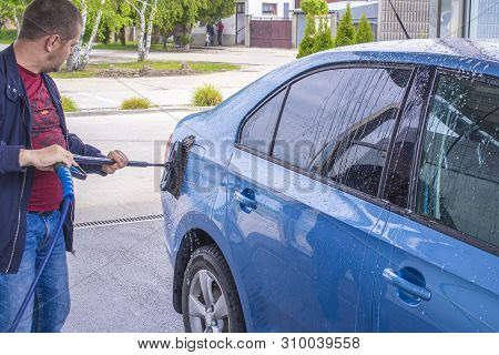 poster of Using A Brush To Wash A Car On A Car Washing Facility On Sunny Summer Day.manual Car Wash With Press