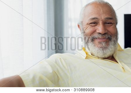 Portrait close up of senior mixed race man smiling inside room. Authentic Senior Retired Life Concep poster