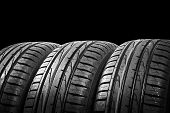Studio Shot Of A Set Of Summer Car Tires Isolated On Black Background. Tire Stack Background. Car Ty poster