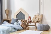 Stylish Kids Bedroom In Tenement House. Grey Pouf On The Parquet, Wooden Table With Bags And Toys,  poster