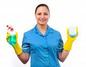 Smiling cleaning lady holding bottle of detergent in one hand and sponge in the other isolated on wh