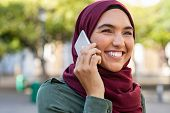 Young woman wearing hijab talking on cellphone in city park. Beautiful muslim girl talking on a mobi poster