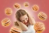 Diet Concept. Frightened Girl In The Stress And Flying Around The Burgers