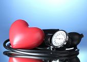 Tonómetro negro y corazón sobre fondo azul