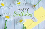 Happy Birthday Inscription. Natural Daisies On A Wooden Background With The Inscription Happy Birthd poster