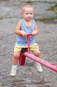 Smiling boy sitting on teeter on the playground on cloudy summer day