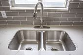 Double Bowl Stainless Steel Sink Undermounted On The White Kitchen Countertop poster