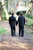 Zwei Homosexuell männlich Bräutigam gehen hand in hand hinunter einen Garten Weg zusammen.  Symbolisiert den Weg des lif