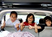 Smiling happy children in car with thumb up