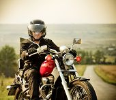 stock photo of biker  - Biker on the country road against the sky - JPG