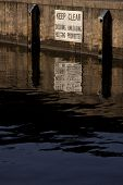 A sign posted above the water line at a city dock that warns boaters to Keep Clear - Docking, Unload