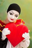 Valentine Pierrot in love holding a red heart