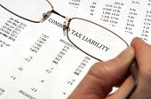 Hand holding magnifying glasses showing the words tax liability on financial paper