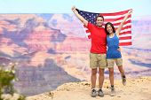 USA travel tourist couple holding american flag in Grand Canyon. Happy young multiethnic couple chee