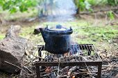 Black Old Smoked Teapot On The Campfire On Picnic In Wood In The Summer