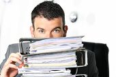 stock photo of stubborn  - busy man hiding behind a stack of files - JPG