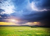 Meadow in mountain. Rain cloud and lightning. Nature composition.