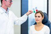 Optometrie Konzept - hübsche junge Frau, die ihre Augen untersuchen durch ein Auge Arzt/Augenarzt (Farbe