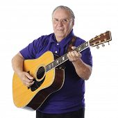 A happy senior man playing his guitar.  On a white background.
