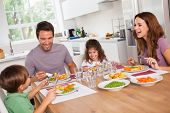 stock photo of pea  - Family laughing around a good meal in kitchen - JPG