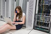 Woman checking the servers with laptop and talking on phone in data center