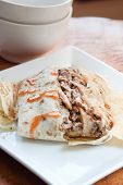 stock photo of jerk  - Caribbean style jerk chicken served in traditional roti and drizzled with sweet hot sauce - JPG