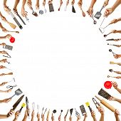 Background frame with many hands holding different kitchen tools in a circle