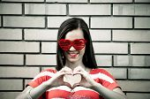Beautiful young brunette with heart-shape eyeglasses make heart with fingers, with brick wall in the