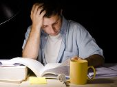 picture of overwhelming  - Young Man Studying at Night isolated on black background - JPG