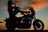 image of dirt-bike  - A silhouette of a woman sitting on her bike relaxing and looking out to the sky - JPG