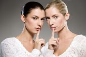 two young caucasian women gesturing shh - keep it secret