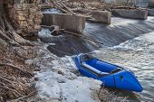 a packraft (one-person light raft used for expedition or adventure racing) below a diversion dam  -