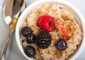 Bowl of delicious steel cut oats with fresh fruit, honey