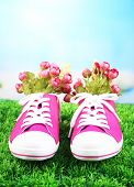 Beautiful gumshoes with flowers inside on green grass, on bright background