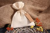 Textile sachet pouch with dried flowers, herbs and berries on wooden table, on sackcloth background