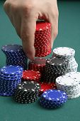 Hand stacking gambling chips on green background