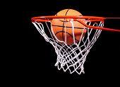 Basketball in hoop on black background