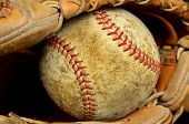 Worn old baseball in brown leather mitt or glove
