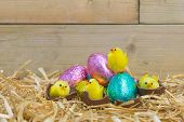 Toy Easter chicks hatching from chocolate eggs in a straw nest.